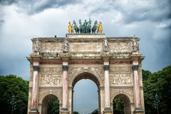 凯旋门du Carrousel在巴黎,法国 成拱形纪念碑和绿色树在多云天空 和平胜利的建筑标志 库存图片
