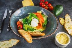 凯萨色拉用鸡蛋、三文鱼、鲕梨、西红柿和烤多士,看法的关闭 在咖啡馆的鲜美食物 免版税库存照片