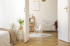 凳子的植物在白色卧室内部的床旁边与在地毯和摇篮的摇马 免版税图库摄影