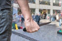 凶手或凶手攻击与刀子在公共场所 图库摄影