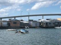 凹下去的小船在恶劣的奔跑后的水中在房子下 免版税库存照片