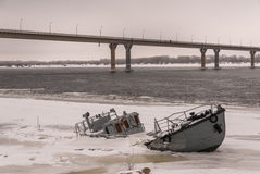 凹下去的小船在一条冻河 免版税库存图片