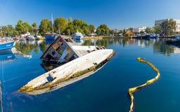 凹下去的小船在埃莱夫西纳港口, Attica,希腊 免版税库存图片