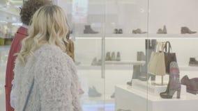 出去为购物的妇女在获得的购物中心乐趣,当检查鞋子在窗口商店-时 影视素材