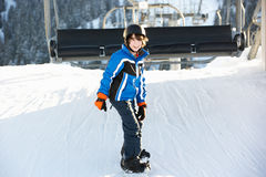 出发在滑雪节假日的新男孩升降椅 免版税图库摄影