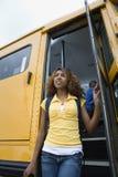 出发校车的高中女孩 免版税图库摄影