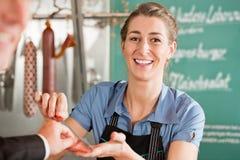 出售肉的俏丽的屠户对客户 免版税库存照片