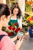 出售花客户的妇女卖花人支付看板卡 免版税库存照片