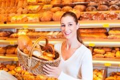 出售面包的女性面包师在她的面包店 免版税库存图片