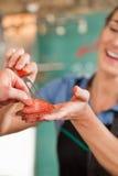 出售鲜肉的女性屠户对客户 免版税库存图片