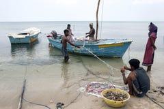 出席他们的在德尔福特海岛上的网的渔夫和妇女在贾夫纳的北方地区在斯里兰卡 免版税库存照片