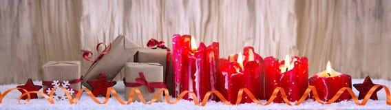 出现和圣诞节礼物的四个红色灼烧的蜡烛 库存照片