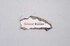 出现在被撕毁的纸后的词沈默凶手 免版税库存照片