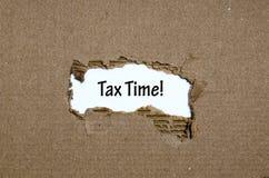 出现在被撕毁的纸后的词税时间 免版税库存照片
