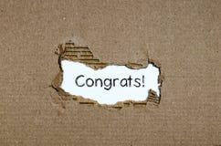 出现在被撕毁的纸后的词congrats 免版税图库摄影