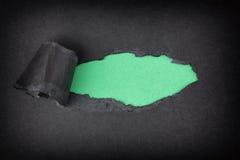 出现在被撕毁的黑纸后的绿皮书背景 库存图片