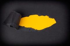 出现在被撕毁的黑纸后的黄色纸背景 库存照片