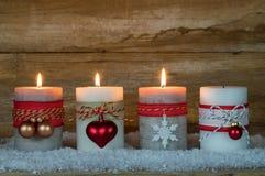 出现季节,在雪的三个灼烧的蜡烛 免版税库存图片