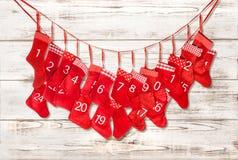 出现日历动画片圣诞节要素图标计时多种 在明亮的木背景的红色长袜 免版税库存图片
