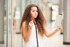 付出由信用卡的美丽的女孩 免版税库存照片
