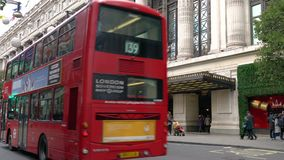 出租汽车和红色双层汽车伦敦公车运送驾驶过去Selfridges,牛津街道,伦敦,英国 股票录像