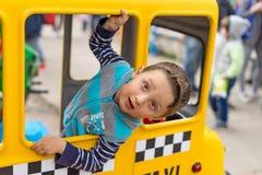 出租汽车的惊奇的乌克兰男孩在照相机看 孩子的夏天活动 微笑 库存照片
