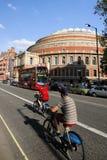出租自行车的游人,通过皇家阿尔伯特霍尔 库存图片