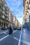 出租车、私家车和一名摩托车骑士在一好日子在巴塞罗那走在路的街道和步行者 免版税库存照片