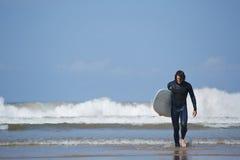 出去年轻冲浪者体育的人运载他的水橇板和海 库存照片