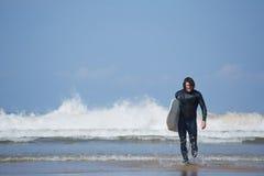 出去年轻冲浪者体育的人运载他的水橇板和海 库存图片