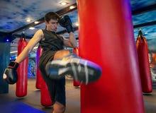 击中一个巨大的吊袋的人拳击手在一个把装箱的演播室 艰苦训练人的拳击手 由吊袋,黑ba的泰国拳击手拳打反撞力 免版税库存图片