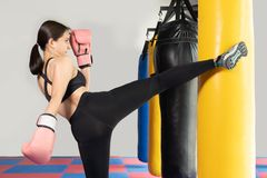击中一个巨大的沙袋的女性拳击手在拳击演播室 艰苦训练妇女的拳击手 由吊袋,Bla的泰国拳击手拳打反撞力 免版税库存照片