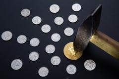 击中与锤子的金黄bitcoin硬币和射线去由的银币做成由中心在黑背景 库存图片