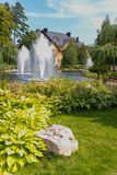 击中在一个现代房子的背景的一个池塘中间的镜子清楚和透明喷泉在公园 免版税库存照片