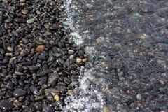 击中在一个美丽的海滩的波浪岩石 库存图片