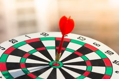 击中在掷镖的圆靶的目标中心的箭箭头 概念对市场成功的企业目标 免版税库存图片