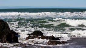 击中在沙滩冲浪者的海浪岩石在背景中 股票视频