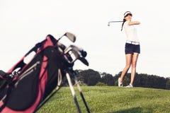 击中在高尔夫球场的女孩高尔夫球运动员球。 免版税库存照片