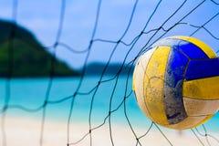 击中对在迷离海滩和蓝色海的网的排球 免版税图库摄影