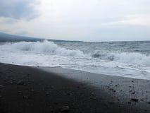 击中巴厘岛的含沙黑火山的沙滩波浪、海浪和海泡沫 在Amed,海是安静,但是在附近的波浪 免版税库存照片