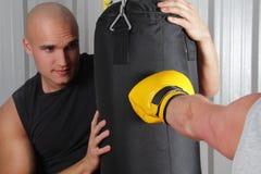 击中打孔机的袋子拳击手 图库摄影