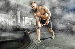 击中有锤子爬犁的体育肌肉人轮子轮胎在健身房 免版税库存图片