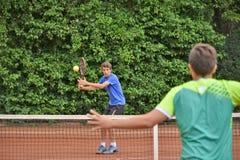 击中正手击球的男性少年网球员 图库摄影