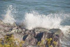 击中海岸线岩石的浪花 库存照片