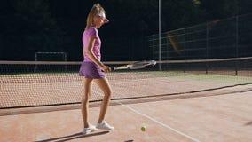 击中球的可爱的女性网球员对地面使用球拍 影视素材