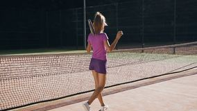 击中球的后面观点的英俊的女性网球员对地面使用球拍 股票视频