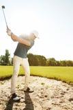击中球的高尔夫球运动员在沙子地堡外面 库存照片