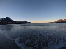 击中白色结冰的沙滩在北极圈的晚秋天的美丽的镇静蓝色波浪与深山和公海竞争 免版税库存照片