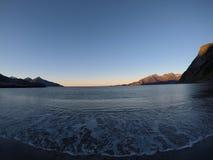 击中白色结冰的沙滩在北极圈的晚秋天的美丽的镇静蓝色波浪与深山和公海竞争 免版税库存图片