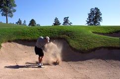 击中砂槽的高尔夫球运动员 免版税库存照片